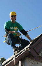 Brian with Denver Gutter Cleaning roped off on a roof