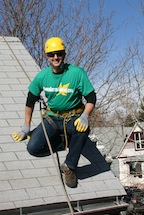 Brian of Denver Gutter Cleaning roped off of a roof wearing a harness and helmet