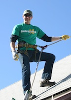 Brian Flechsig of Denver Gutter Cleaning roped off on a roof to clean a gutter